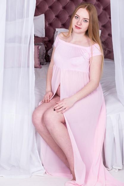 Mulher grávida no vestido rosa, sentada na cama. conceito de gravidez, descanso, pessoas e expectativa Foto Premium