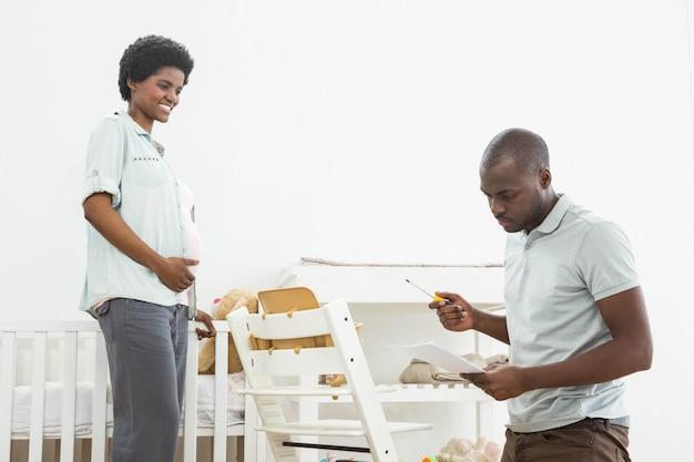 Mulher grávida olhando homem lendo uma lista enquanto conserta uma cadeira de bebê em casa Foto Premium