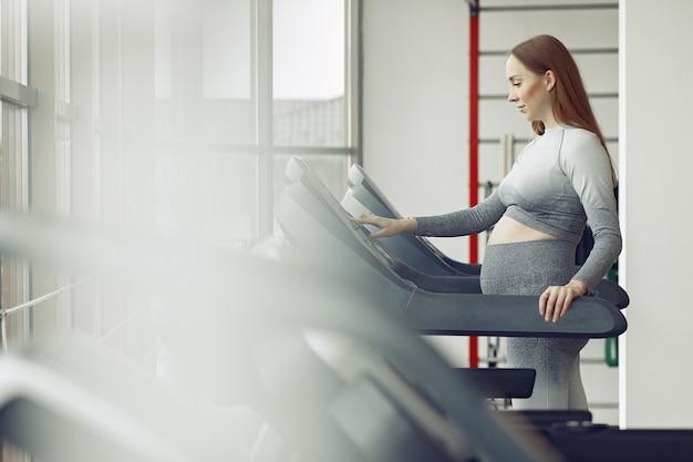 Mulher gravida que treina em uma academia Foto gratuita