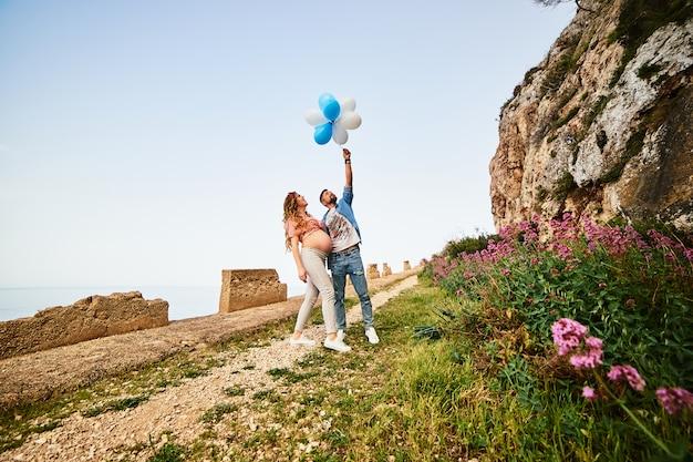 Mulher gravida saudável nova da beleza com seu marido e balões ao ar livre Foto Premium