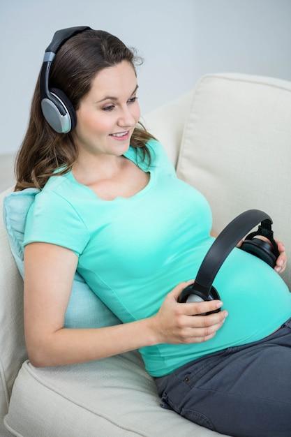Mulher grávida, segurando, headphone, ligado, barriga sofá Foto Premium