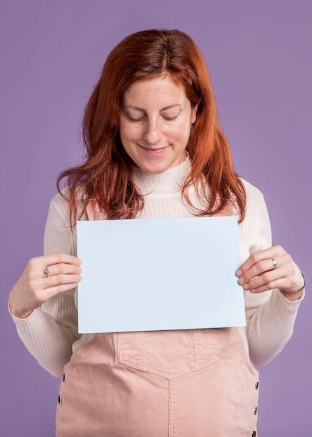 Mulher grávida segurando papel com bebê na mensagem do forno Foto gratuita