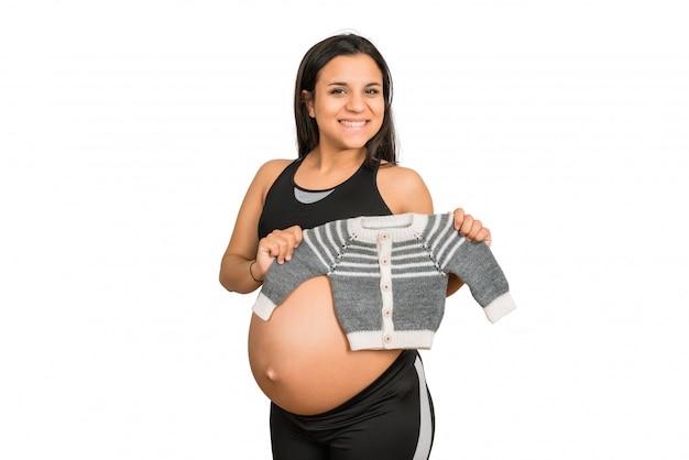 Mulher grávida segurando roupas de bebê. Foto gratuita