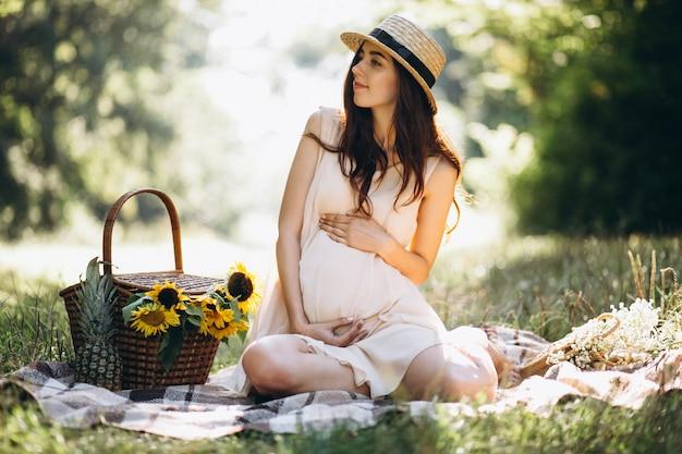 Mulher grávida, tendo piquenique, parque Foto gratuita