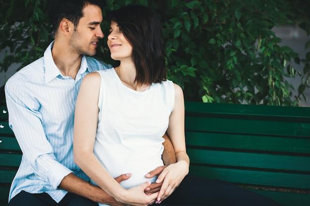 Mulher grávida tocando as mãos do marido Foto gratuita