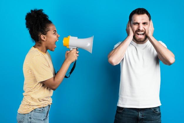 Mulher gritando com homem através de megafone Foto gratuita