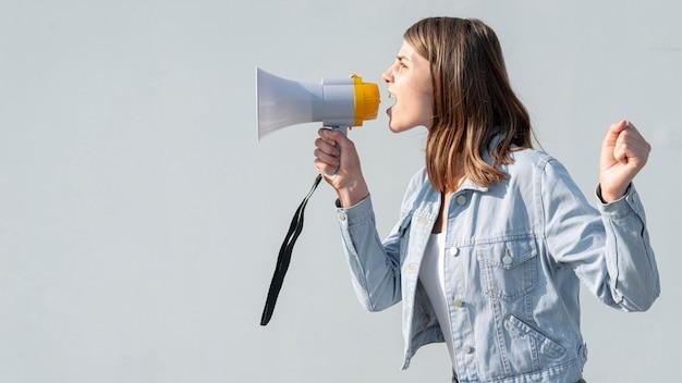 Mulher gritando com megafone na demonstração Foto gratuita