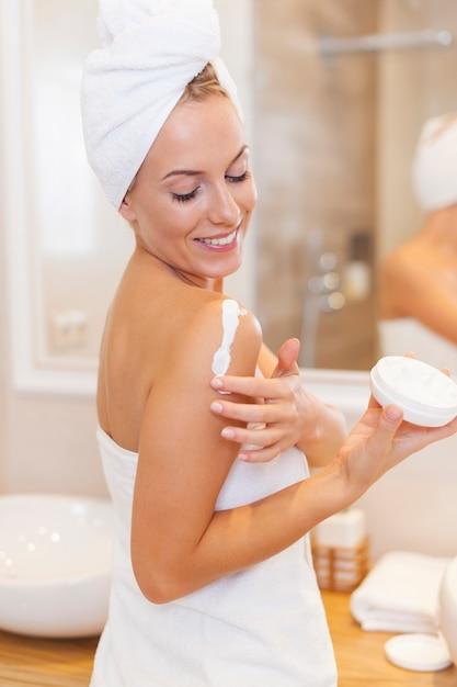 Mulher hidrata o braço após o banho Foto gratuita
