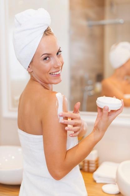 Mulher hidrata o corpo após o banho Foto gratuita