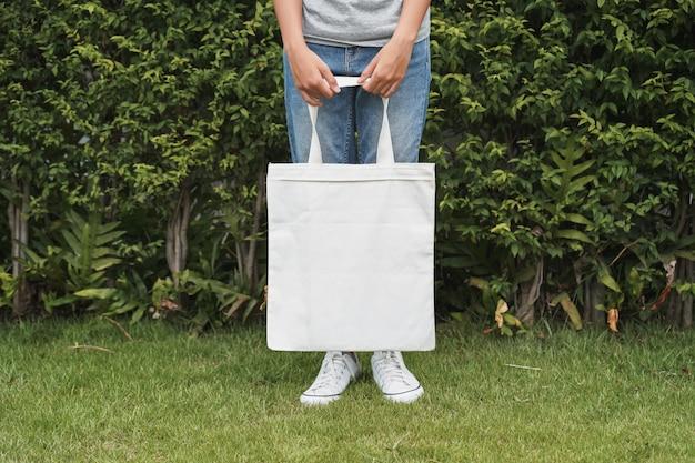 Mulher hipster com saco de algodão branco no fundo da folha verde Foto Premium