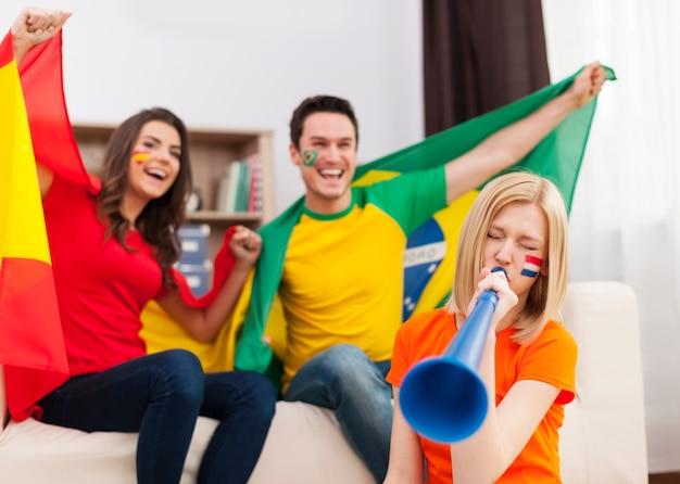 Mulher holandesa soprando vuvuzela durante partida de futebol Foto gratuita