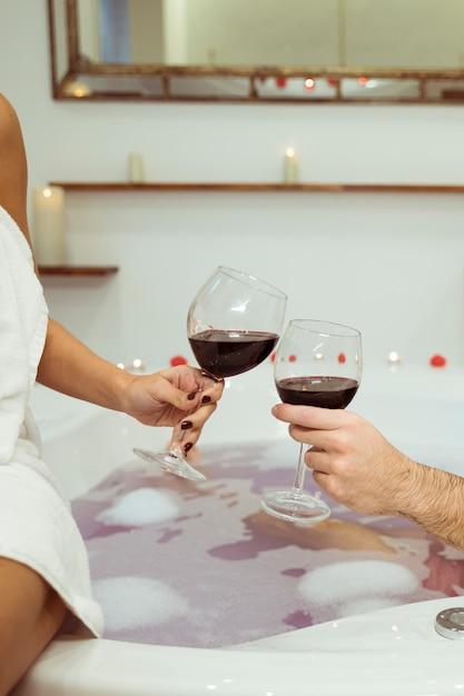 Mulher homem, clanging, copos, de, bebida, perto, água, com, espuma, em, banheira spa Foto gratuita