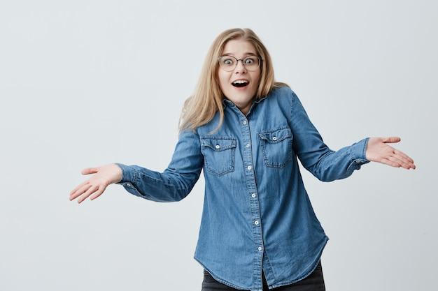 Mulher horrorizada, com cabelos loiros e óculos, gestos de perplexidade, chocada, surpresa ao lembrar que se esqueceu de pagar as contas. mulher frustrada com olhos esbugalhados exclama em pânico Foto gratuita