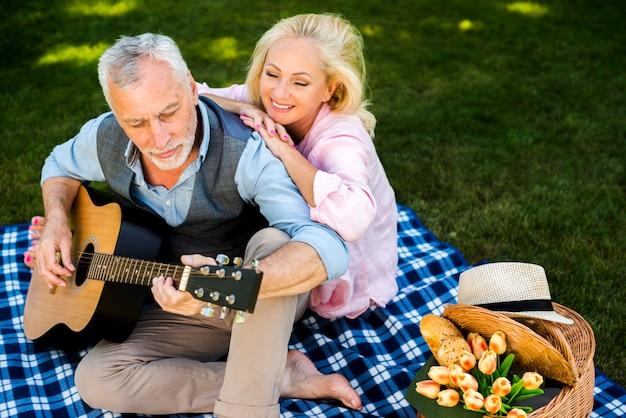 Mulher idosa, apreciando sua música de guitarra de homem Foto gratuita