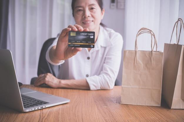 Mulher idosa asiática que mostra a zombaria acima do cartão de crédito, conceito de comprar em linha. Foto Premium