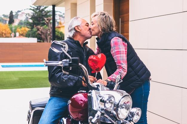 Mulher idosa beijando homem na motocicleta Foto gratuita