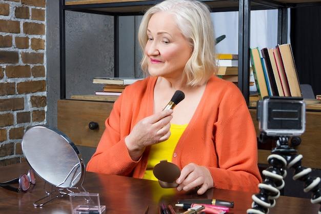 Mulher idosa blogueira gravando ela fazendo maquiagem on-line Foto Premium