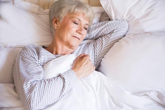 Mulher idosa cansada dormindo na cama Foto gratuita