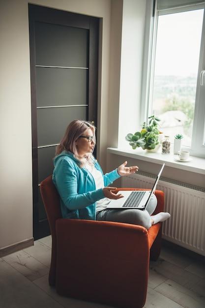 Mulher idosa caucasiana com óculos falando no laptop com alguém e explica enquanto está sentada na poltrona perto da janela Foto Premium