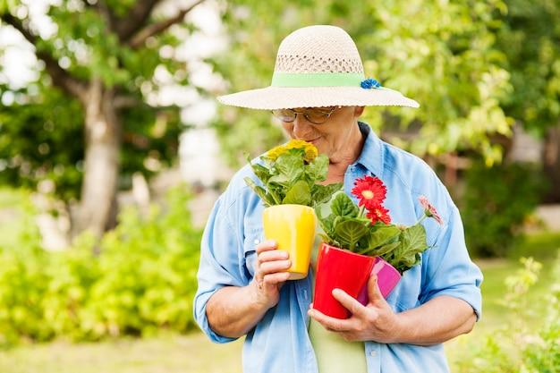 Mulher idosa cheirando flores Foto gratuita