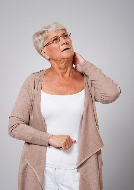 Mulher idosa com dor no pescoço Foto gratuita