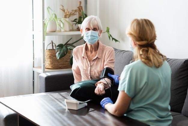 Mulher idosa com máscara médica examinando a pressão arterial em uma casa de repouso Foto gratuita