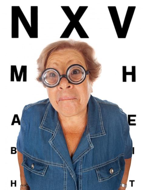 Mulher idosa com mesa para exame oftalmológico Foto Premium