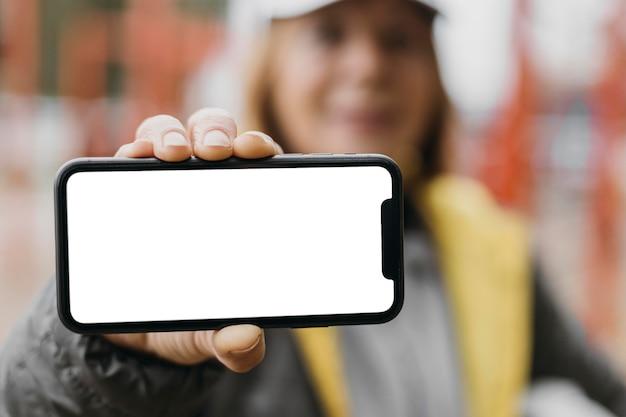 Mulher idosa desfocada segurando smartphone ao ar livre Foto gratuita