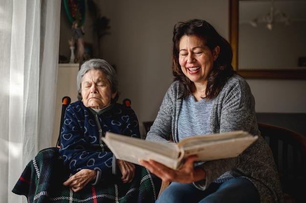 Mulher idosa e doente com perda de memória, sentada na cadeira de rodas. filha sorridente segurando um álbum de fotos, tentando se lembrar. Foto Premium