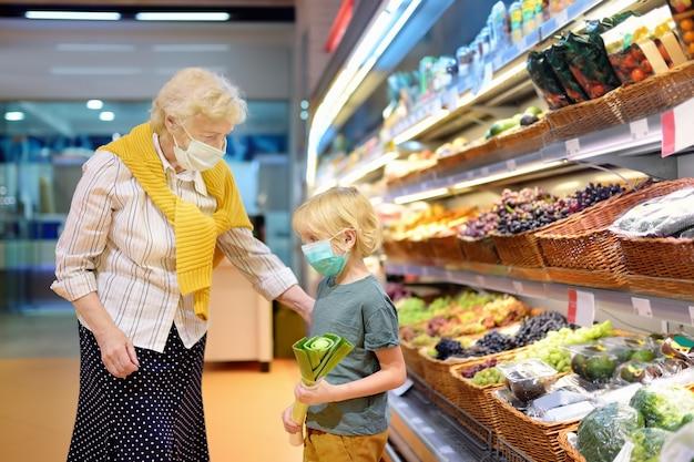 Mulher idosa e neto usando máscara médica descartável em compras Foto Premium