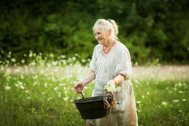 Mulher idosa em um vestido branco segura uma bacia com água. Foto Premium