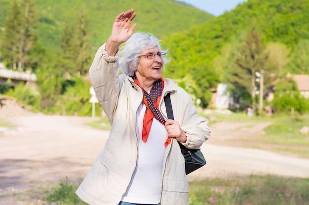 Mulher idosa feliz andando no campo Foto gratuita