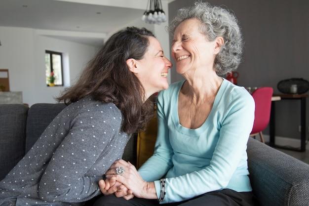 Mulher idosa feliz e sua filha rindo e de mãos dadas Foto gratuita