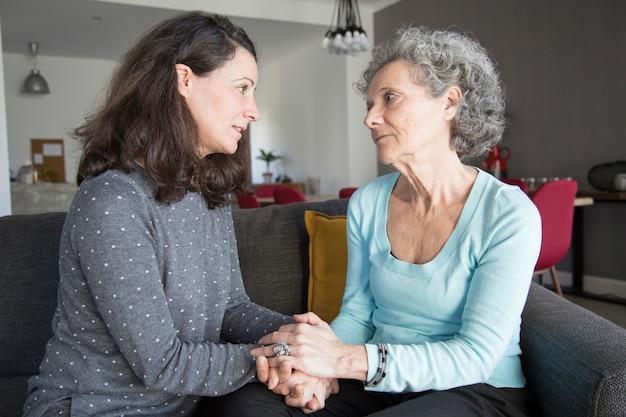 Mulher idosa grave e sua filha conversando e de mãos dadas Foto gratuita