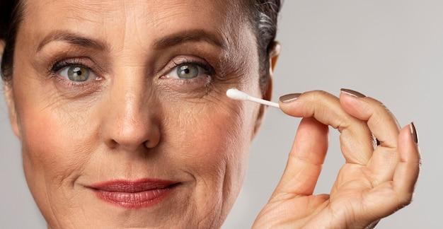 Mulher idosa maquiada usando cotonete para removê-la Foto gratuita