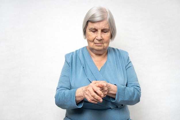 Mulher idosa massageia palmas doloridas Foto Premium