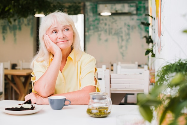 Mulher idosa pensativa, sentado à mesa no café Foto gratuita