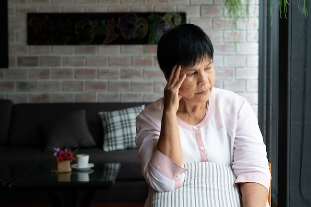Mulher idosa que sofre de dor de cabeça, estresse, enxaqueca, problema de saúde Foto Premium