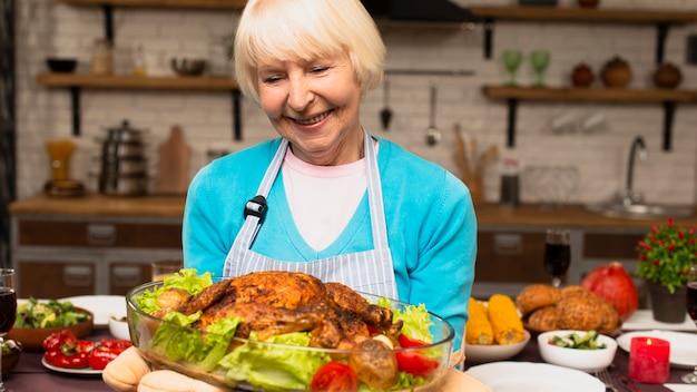 Mulher idosa segurando o peru cozido Foto gratuita