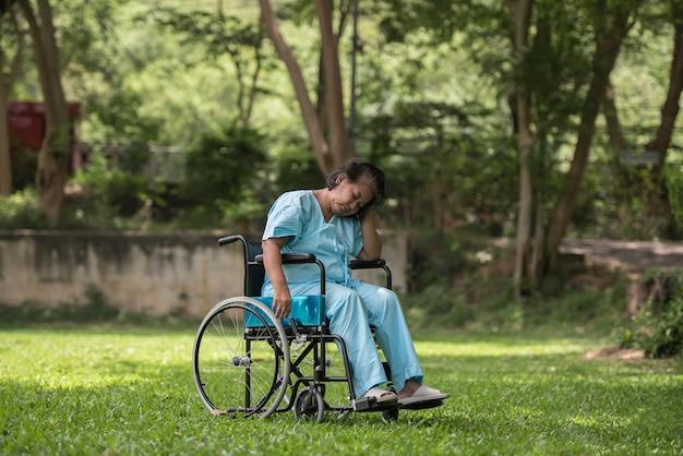 Mulher idosa solitária sentado sentimento triste na cadeira de rodas no jardim no hospital Foto gratuita