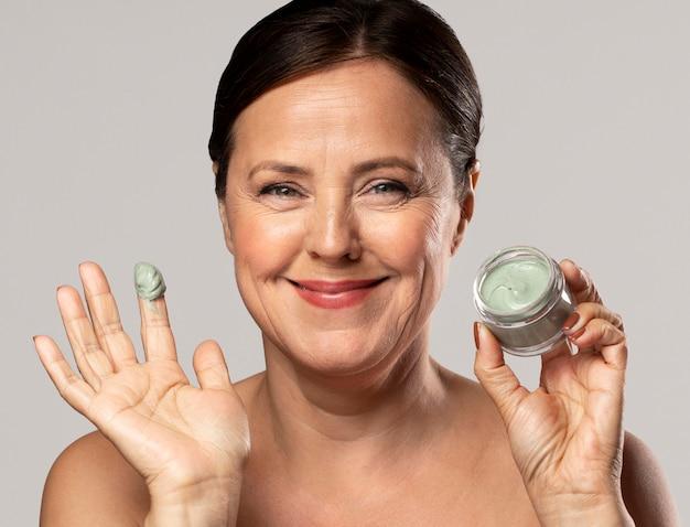 Mulher idosa sorridente usando máscara facial Foto gratuita