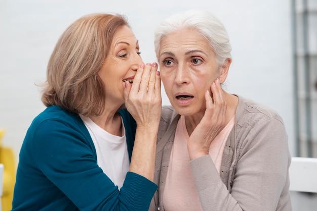 Mulher idosa sussurrando para a amiga | Foto Grátis