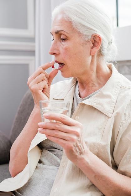 Mulher idosa, tendo, dela, medicinas Foto gratuita