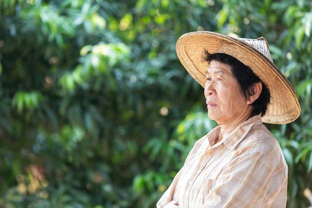 Mulher idosa um fazendeiro que sorri e que realiza no jardim. Foto gratuita
