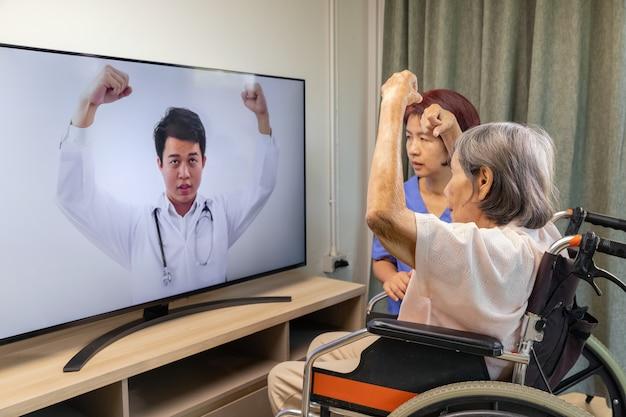 Mulher idosa usando serviço online de fisioterapia em casa. Foto Premium