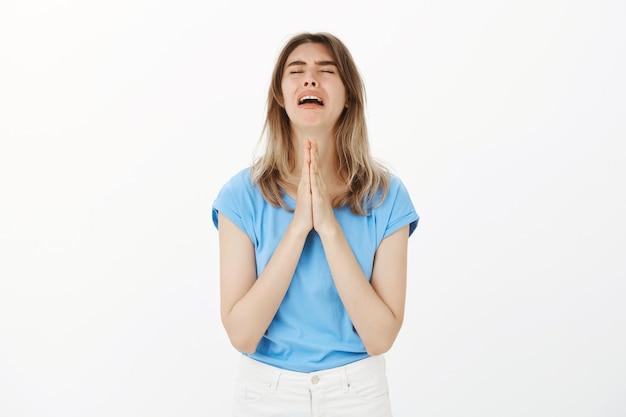 Mulher implorando implorando por ajuda ou orando desesperadamente Foto gratuita