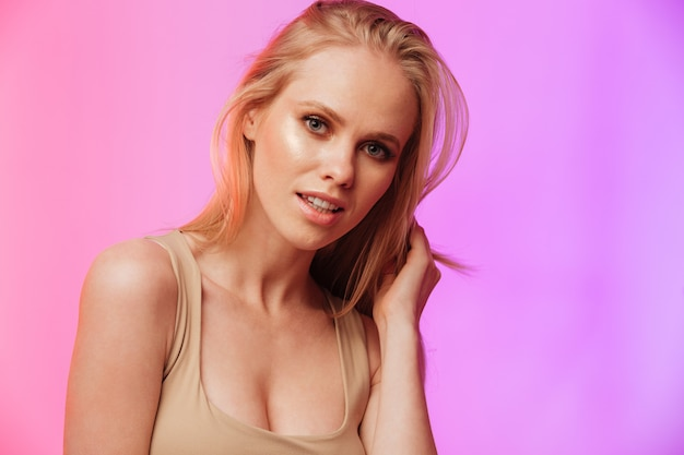 Mulher incrível em pé e posando sobre parede rosa Foto gratuita