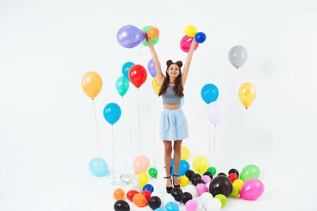 Mulher incrível, olhando em linha reta, segurando balões de hélio em branco Foto gratuita