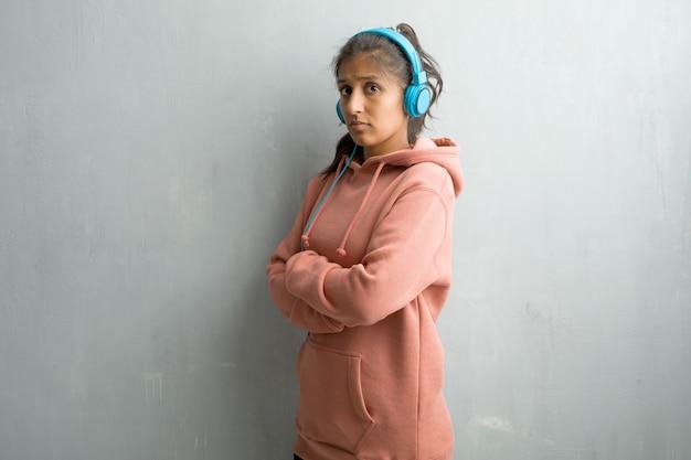 Mulher indiana desportiva nova contra uma parede que cruza seus braços, sérios e imponentes Foto Premium