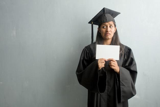 Mulher indiana graduada nova de encontro a uma parede muito scared e receosa, desesperada para algo, gritos do sofrimento e dos olhos abertos, conceito da loucura. segurando um cartaz. Foto Premium